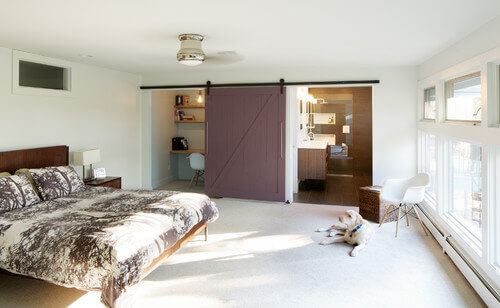 This master bedroom and its dusky plum barn door shows the versatility of the door. When both the bathroom and desk areas need to be open, the door can rest in the middle of the wall between the two rooms.