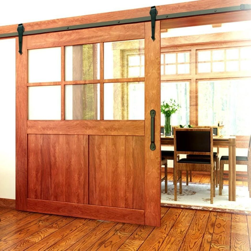 A large wooden barn door, the top half divided into window panes. This allows the light from the dining room to pour through into the adjacent room, while still allowing the door to close off the space.
