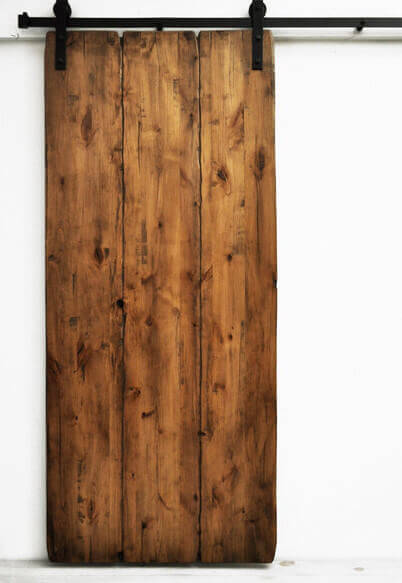 This sliding barn door has no frame, and is constructed out of three stained and aged boards.