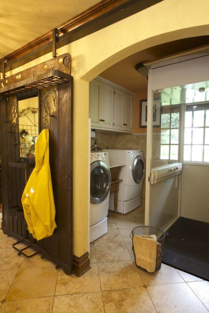 "This incredible ""barn"" door may not be entirely made out of wood, but the sliding hardware allows it to serve the same function as more traditional examples of the style. This door is outfitted with lovely carvings and places to hang coats. The door can be slid in front of the laundry room to hide any messes."