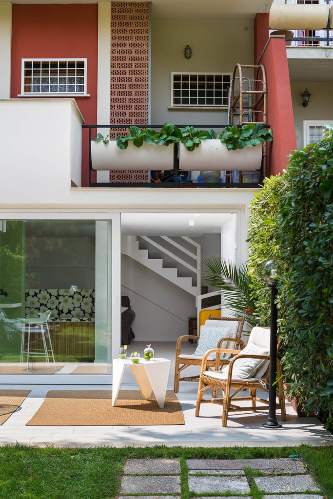 We approach the home from the garden, which reveals the truly open nature of the design, integrating and meshing with the outdoors via broad openings and massive glass panels. The patio furniture acts as an extension of the comfortable living room.