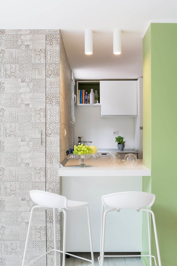 Tucked to the side is this unique dining cove, with open access to the extended kitchen counter on the other side of the wall. A pair of simple white stools offers dining opportunity within the larger room.