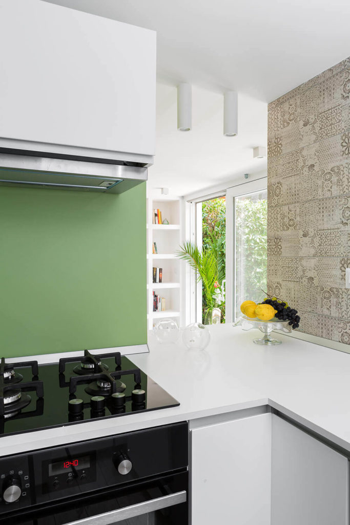 Moving to the other side of the counter, we see that the kitchen is wrapped in sleek white surfaces, with minimalist countertops and cabinetry framing sleek black and stainless steel appliances. The bold green tone and textural floral wallpaper enhances the look.