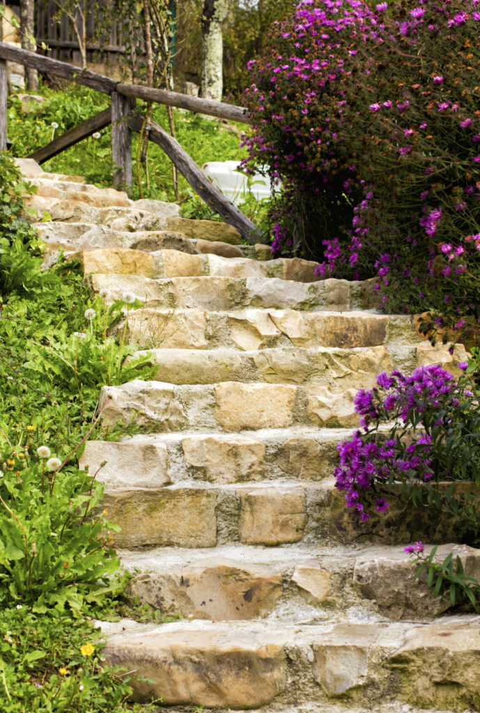Wooden railing also works great alongside stone steps. Raw and natural wood works particularly well with rougher cut and raw stone.