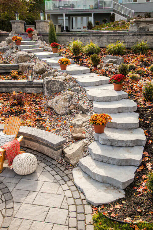 This set of clean stone steps is bright and beautiful. This landscape uses rock gardens, stone patios, and steps to build a vibrant and diverse color profile that is appealing and interesting.