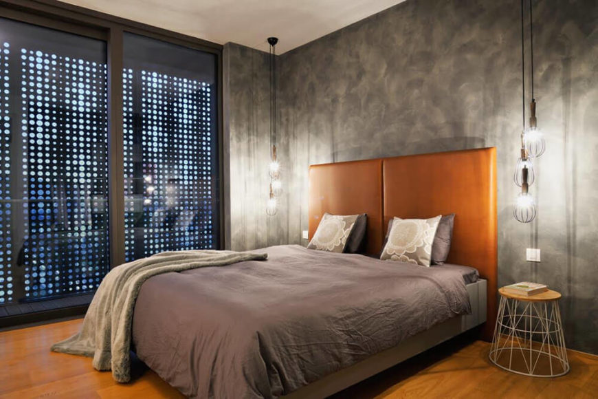 The master bedroom is defined by a more industrial look, with concrete walls exposed an circular shade panels on the windows. The hazelnut headboard helps connect it to the rich hardwood flooring throughout the home.