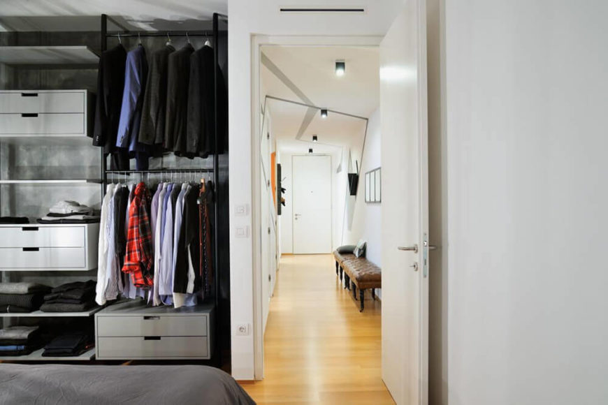 From here we can see the open closet design, making the room feel larger and more dynamic. The lengthy hallway recedes from view toward the front entry and the rest of the home.