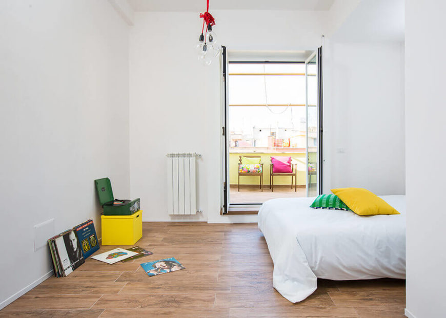Here we have the master bedroom, a white minimalist space with plenty of room for activities. The owner's record collection sits along with a bold yellow box to the left, while we can see the terrace through double doors.